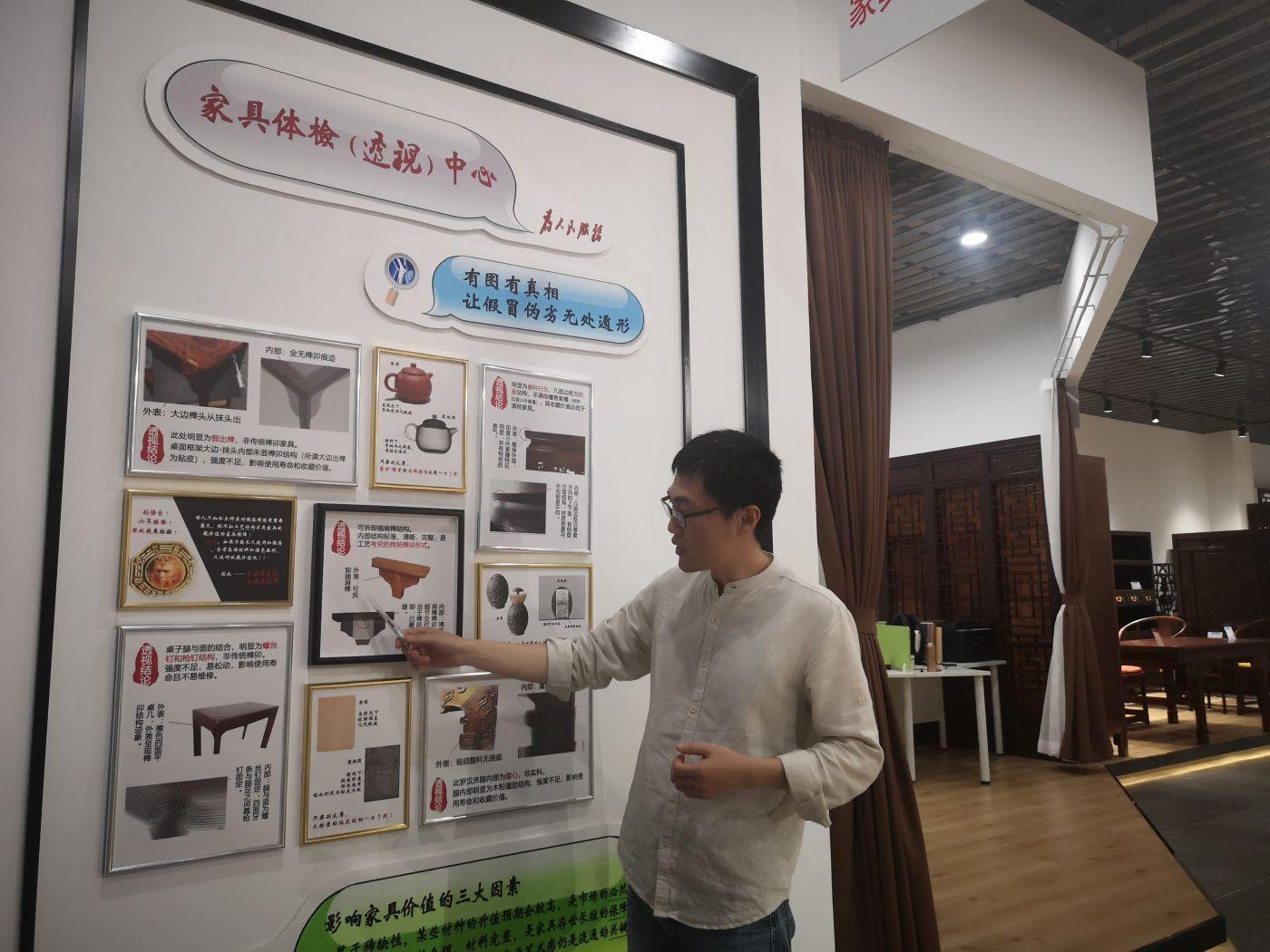中国木材与木制品流通协会红木专委会秘书长汪立禹在展示墙前介绍红木家具造假伎俩