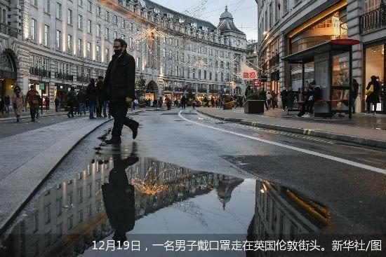12月19日,一名男子戴口罩走在英国伦敦街头。新华社/图